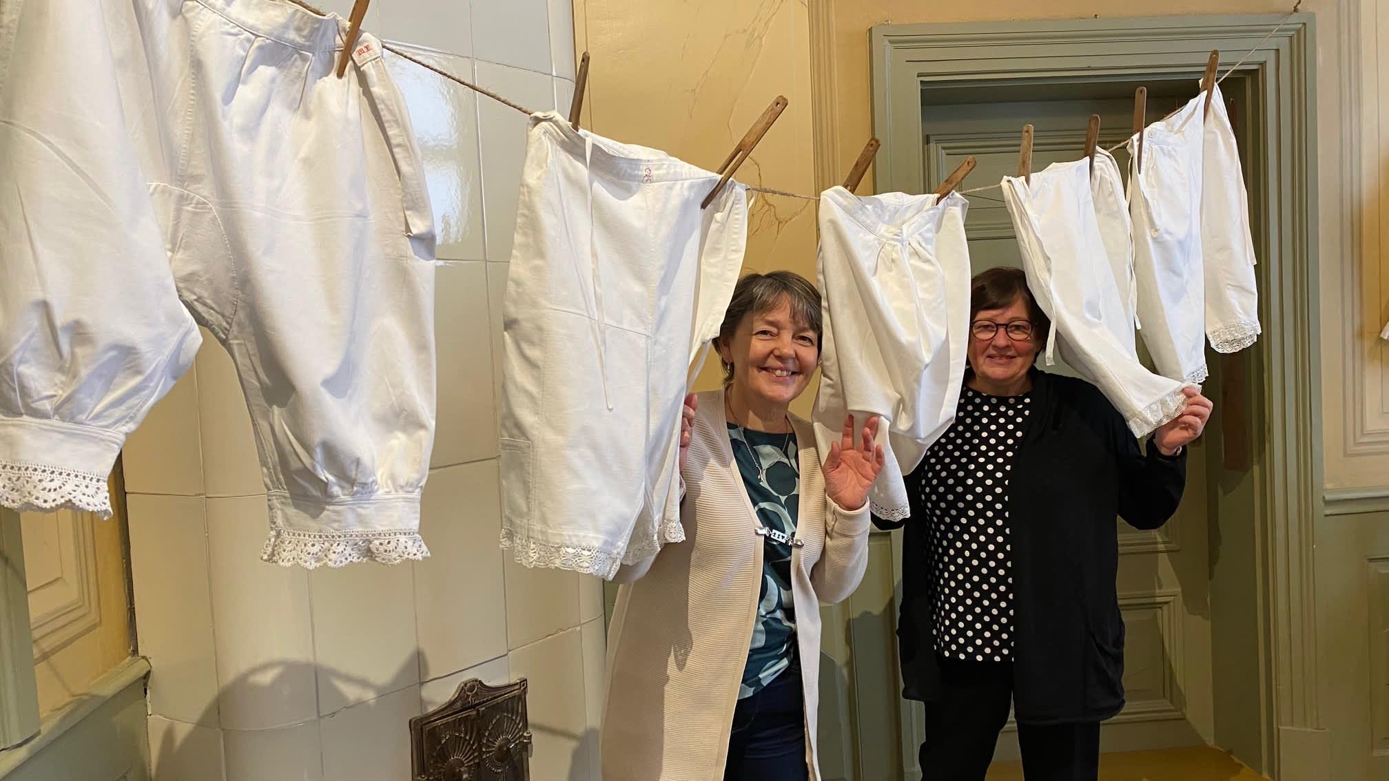 Naisten vanhoja alushousuja narulla. Välistä kurkistelevat museolta Carola Sundqvist ja Ann-Marie Knif-Sandelin