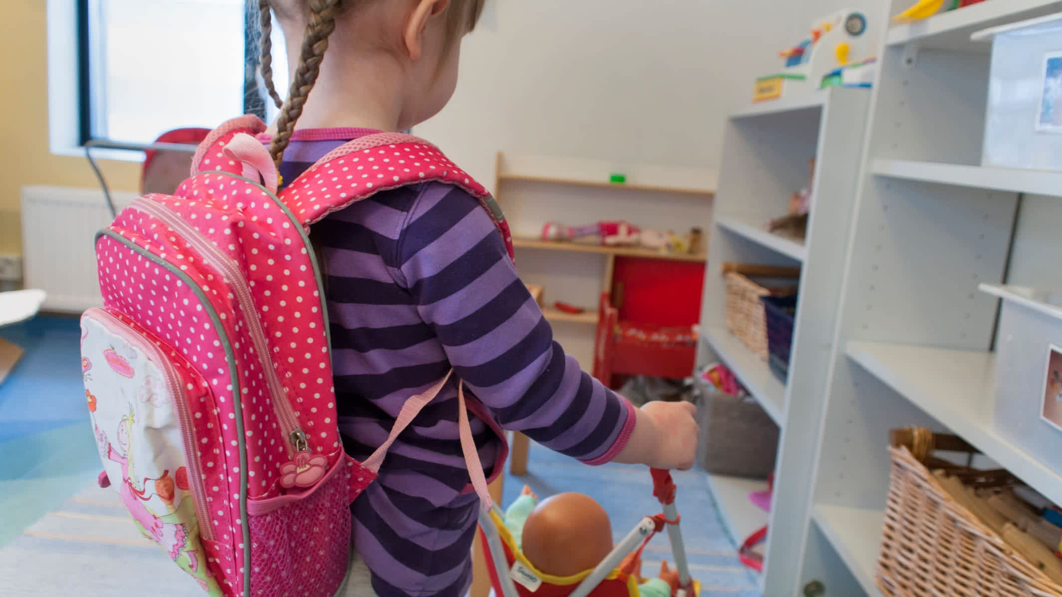 Päiväkodin tyttö leikkii nukeilla.