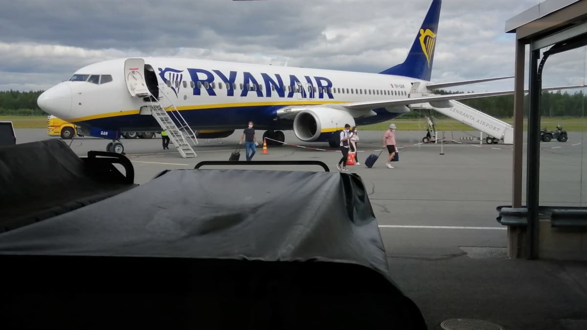 Ryanairin lentokoneesta tulee ihmisiä ulos rauhalliseen tahtii.