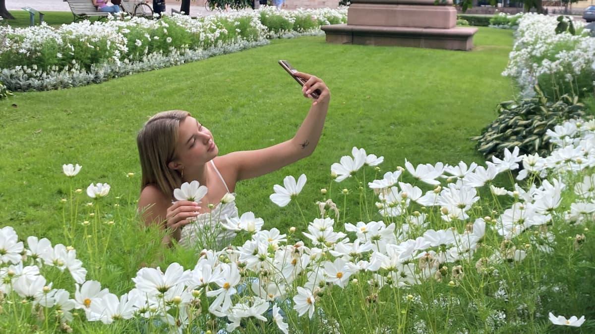 Joalin Loukamaa ottaa itsestään kuvaa kukkien keskellä.