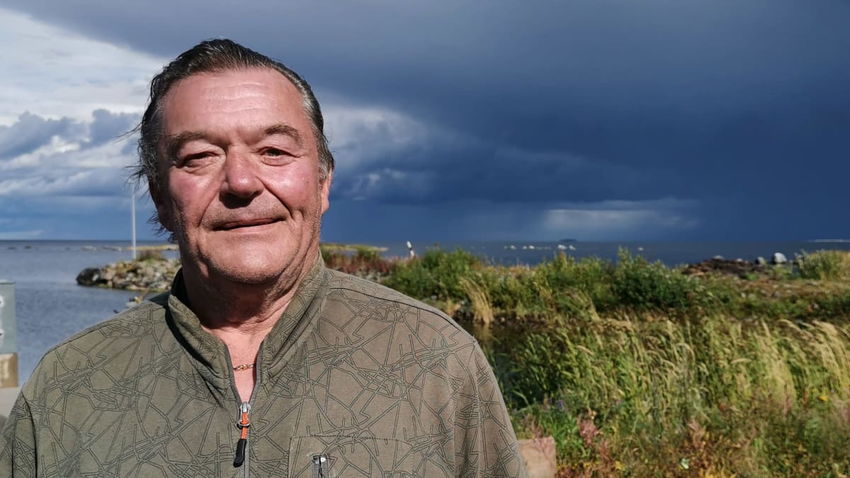 Kalastaja Reino Ruosmeri seisoo Björköbyn kalasatamassa rannalla, taustalla tummia ukkospilviä