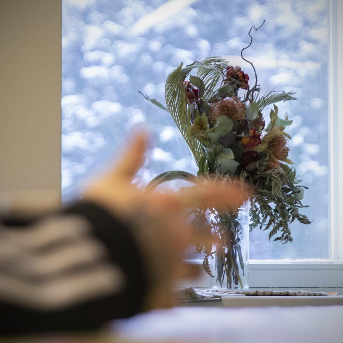 Kurpahtaneita kukkia maljakossa ikkunalaudalla.