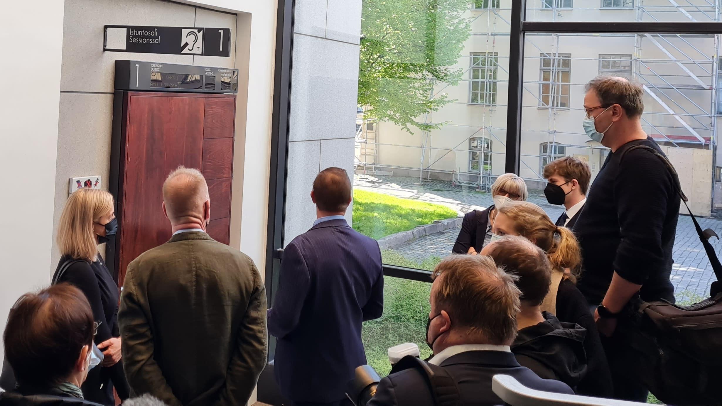 Vastaaja seisoo median ympäröimänä oikeussalin ovella