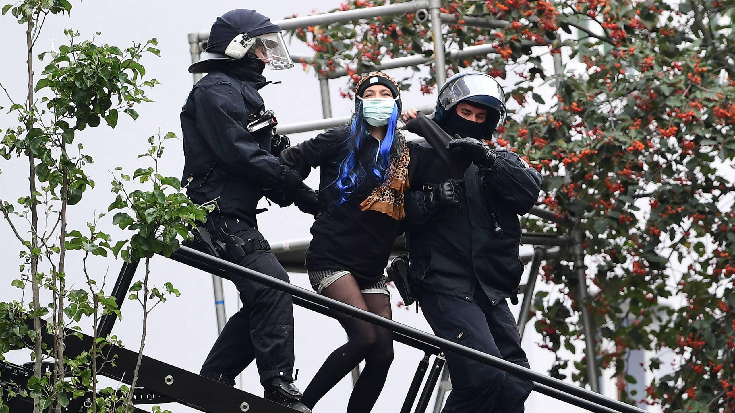 Kaksi poliisia taluttaa talonvaltaajaa alas tikkaita