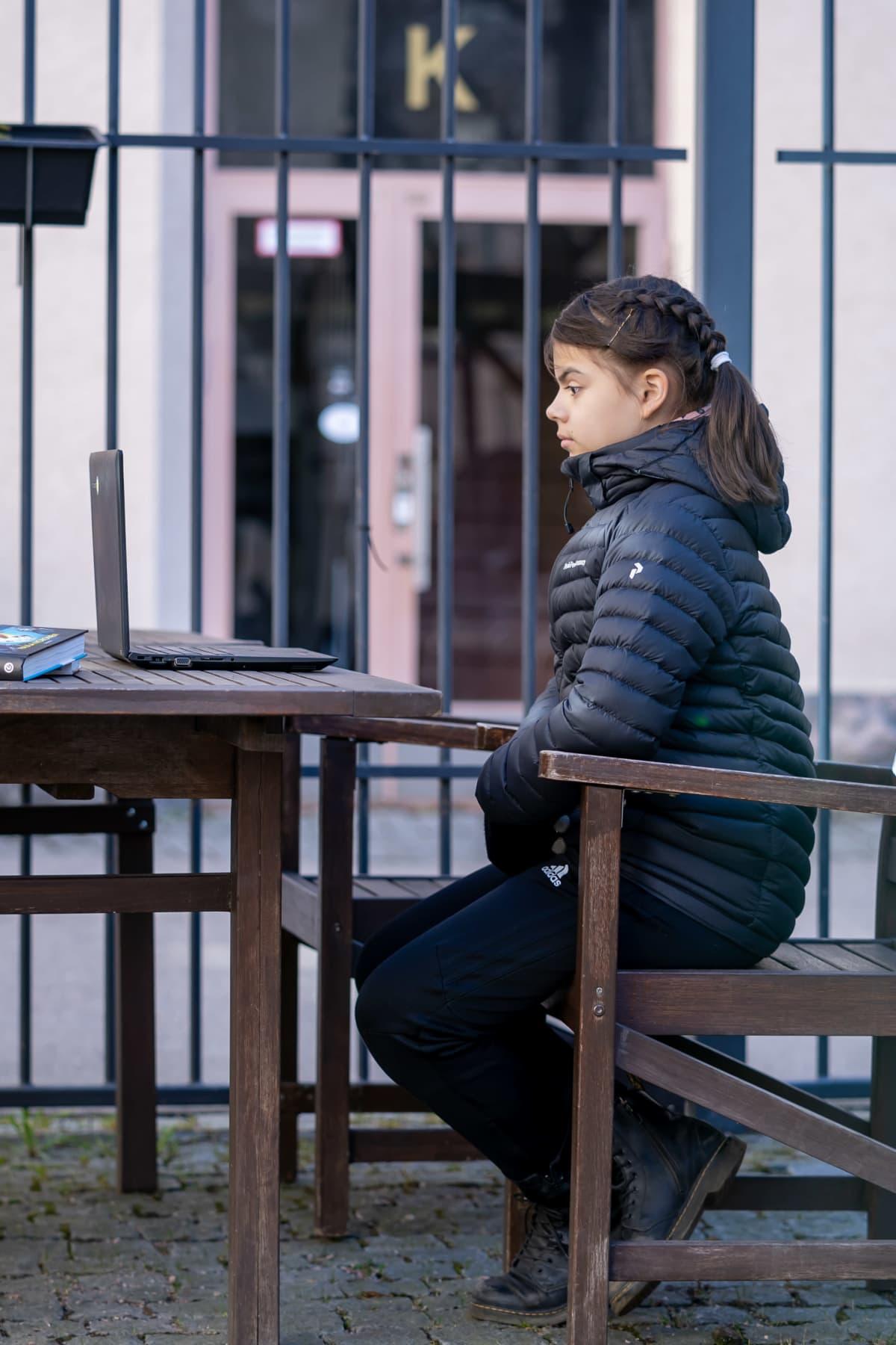 Koululainen Linnea Rimminen seuraamassa kirjailija Paula Norosen virtuaalivierailua kotinsa sisäpihalla, Vallila, Helsinki, 8.4.2020.