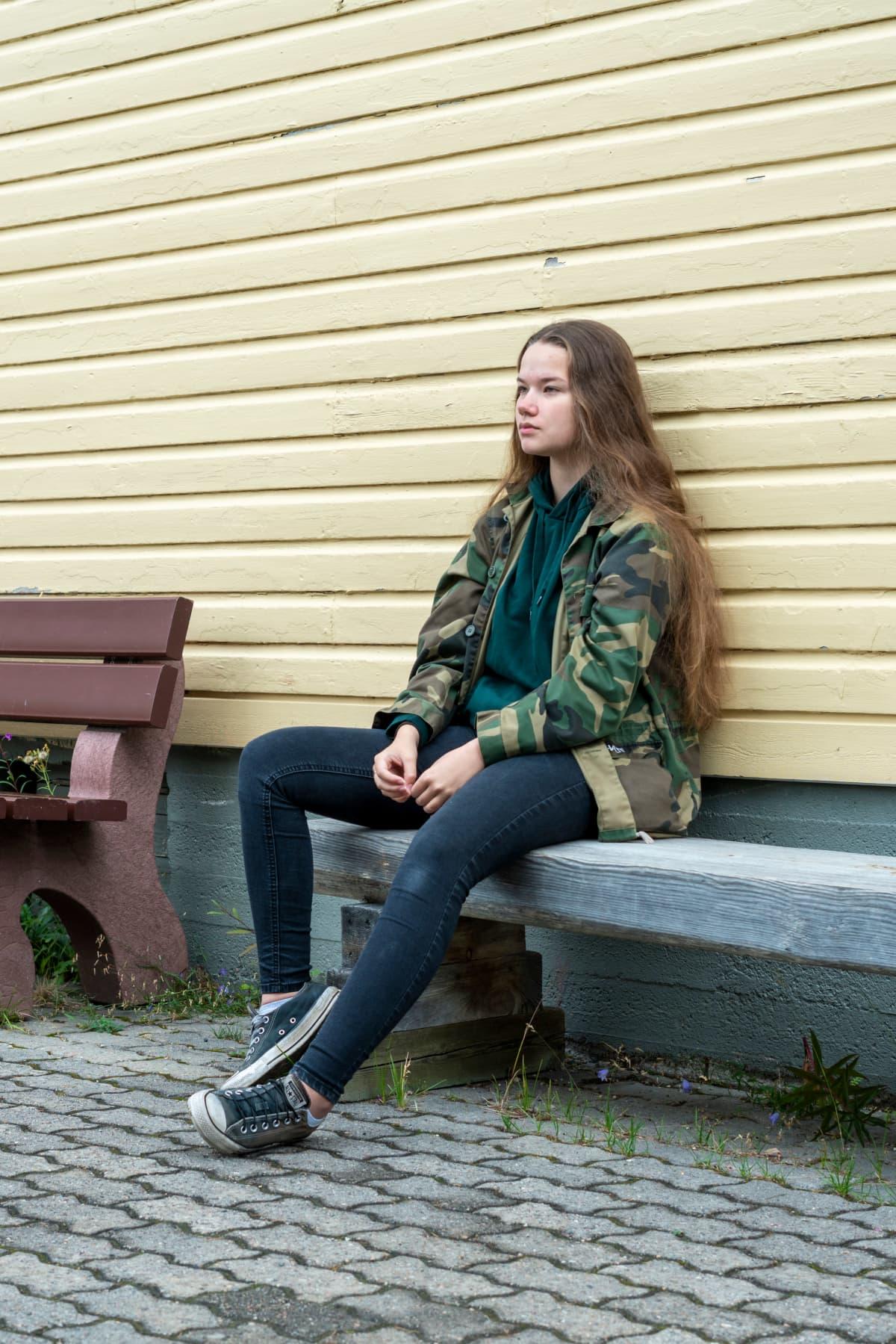 Tyttö istuu penkillä seinän edessä. Hänellä on päällään maastokuviollinen takki.
