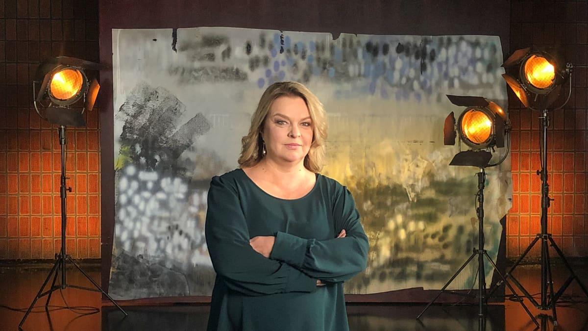 Elina Knihtilä seisoo studiossa taustalavasteen ja studiolamppujen edessä. Kuva otettu lyhytvideosarjaan Me elokuvantekijät.