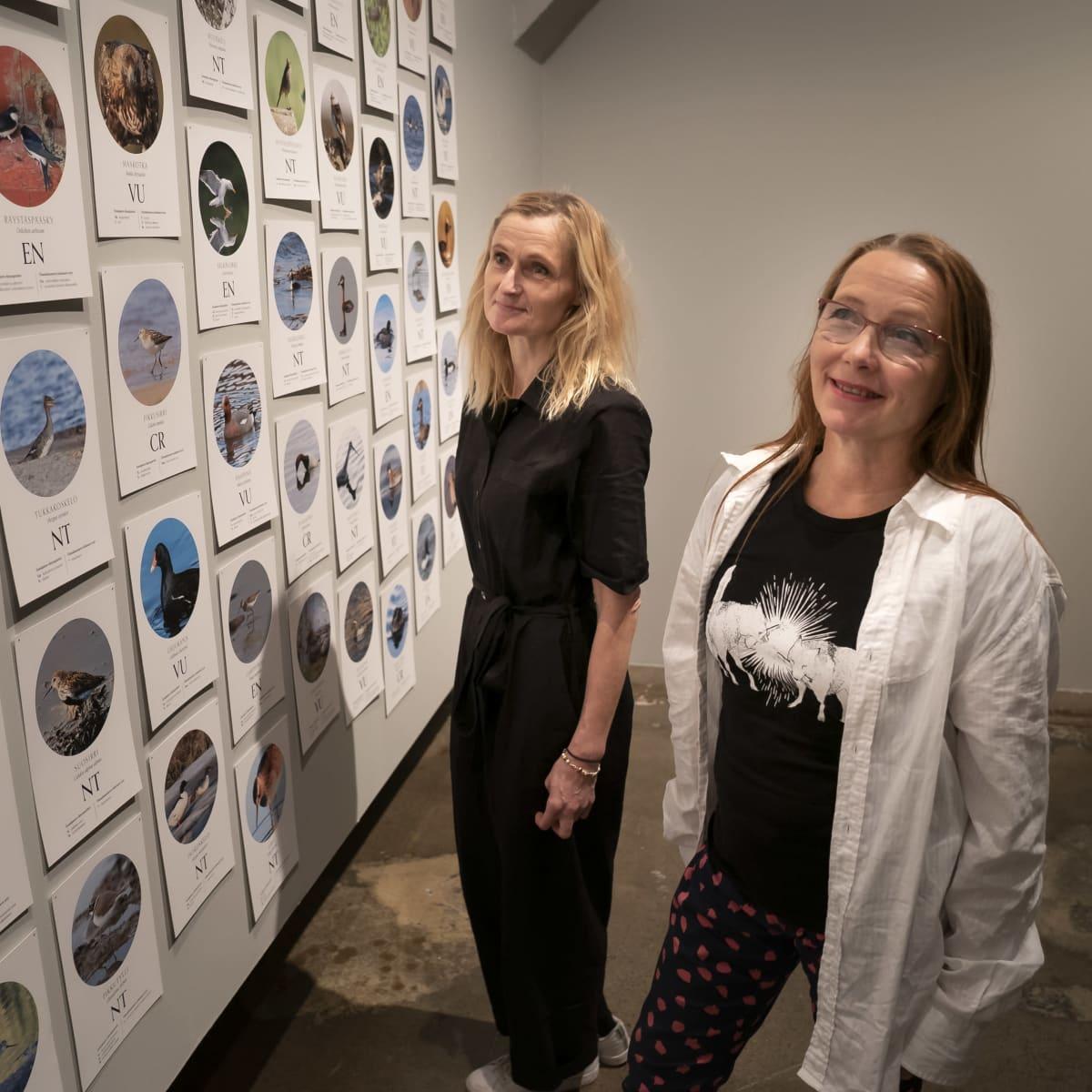 2 naista katselee valokuvia näyttelyssä.