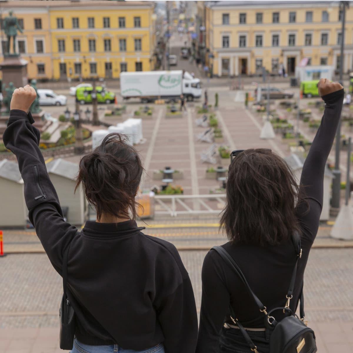 Kaksi naista seisomassa kädet nyrkkiin puristettuna.