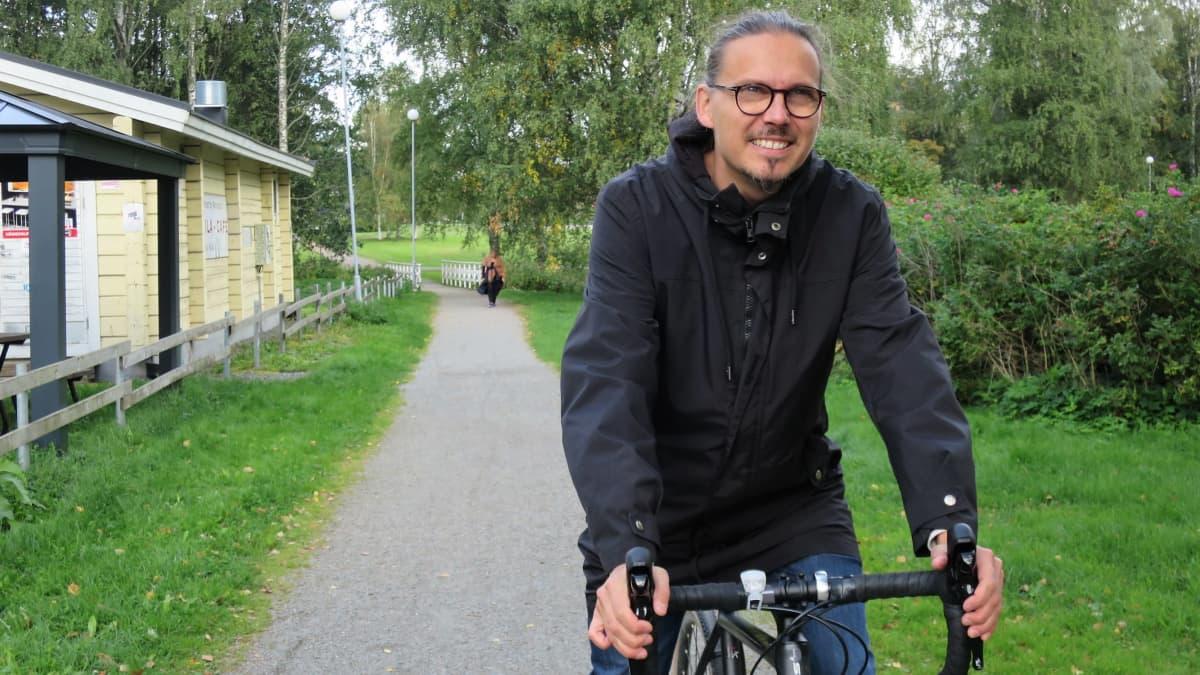 Silmälasipäinen mies ajaa vaihdepyörällä puistotietä pitkin