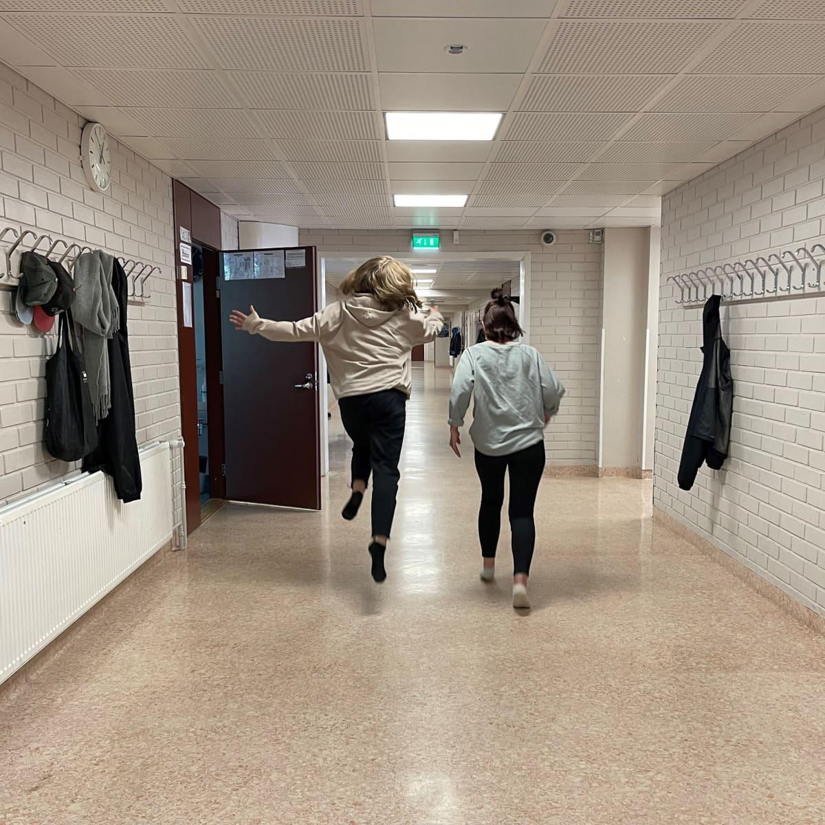 Tytöt juoksevat ja hyppelevät yläkoulun tyhjällä käytävällä