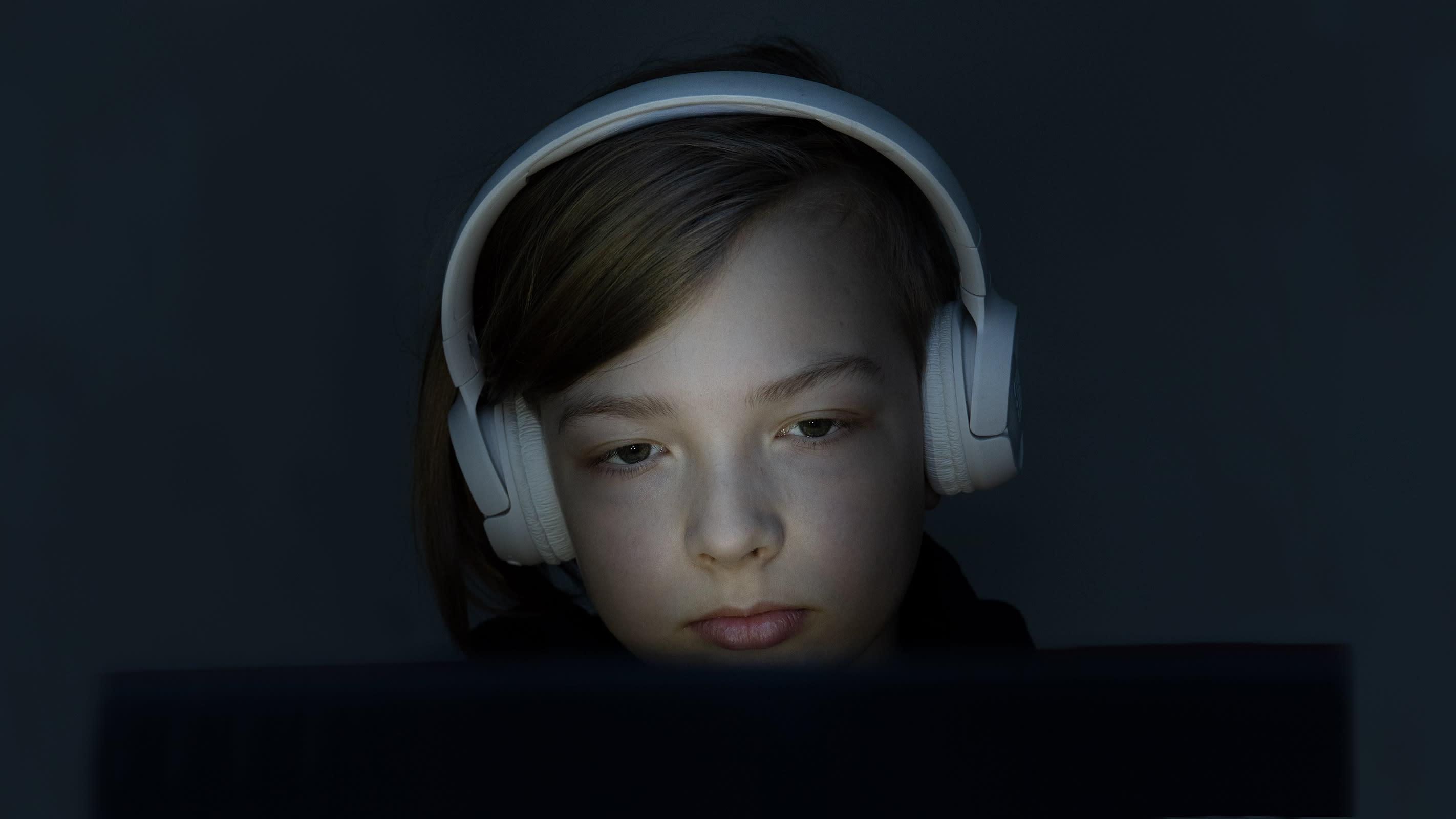 Poika istuu hämärässä tietokoneen ruutua katsoen.