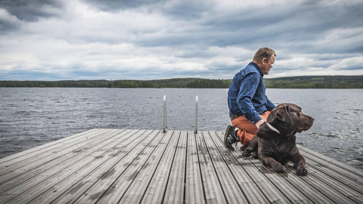 Jarno Akerman koiransa kanssa laiturilla.