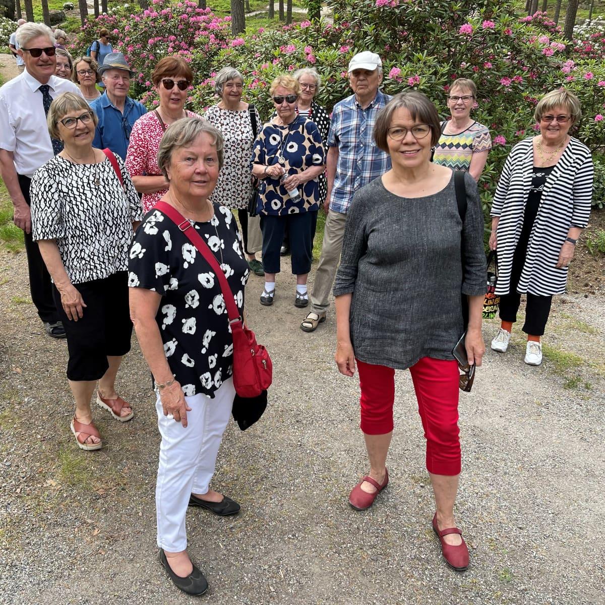 Joukko iloisia eläkeläisiä alppiruusupuistossa