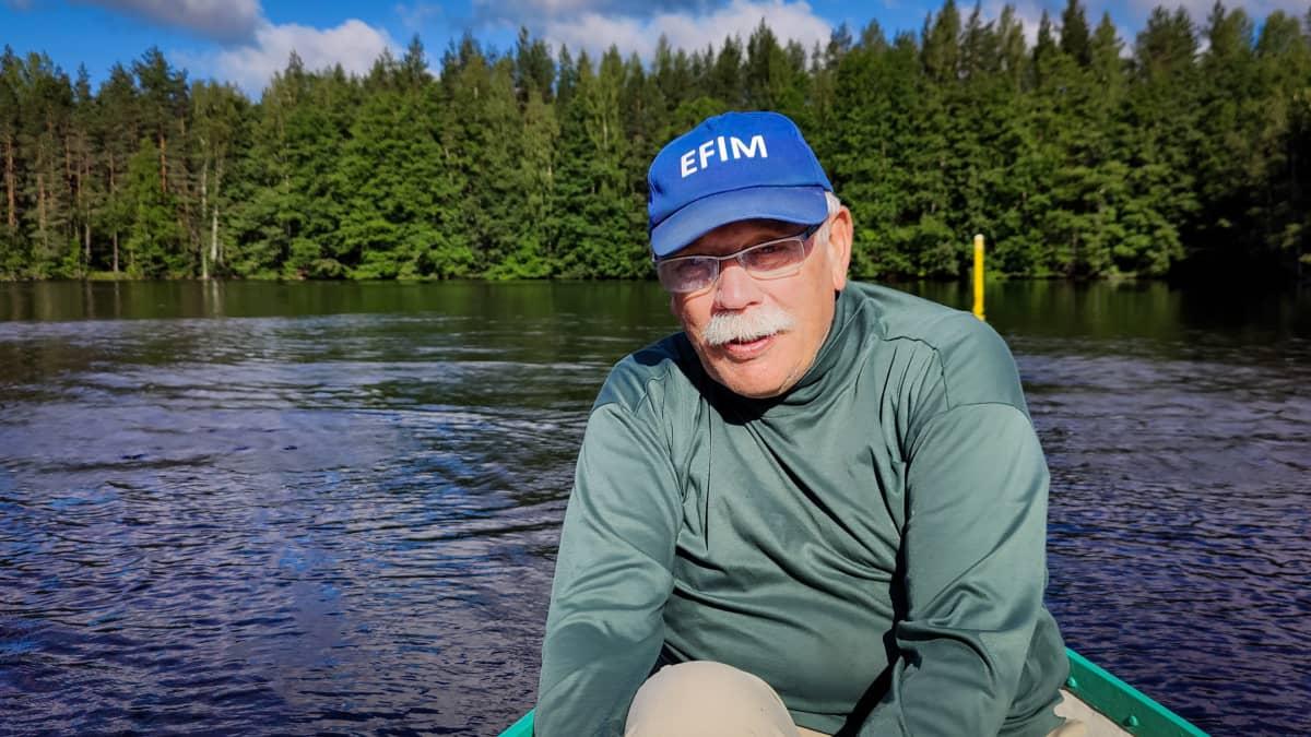 Timo Pankka myhäilee paksujen viiksiensä takaa veneen peräpäässä.