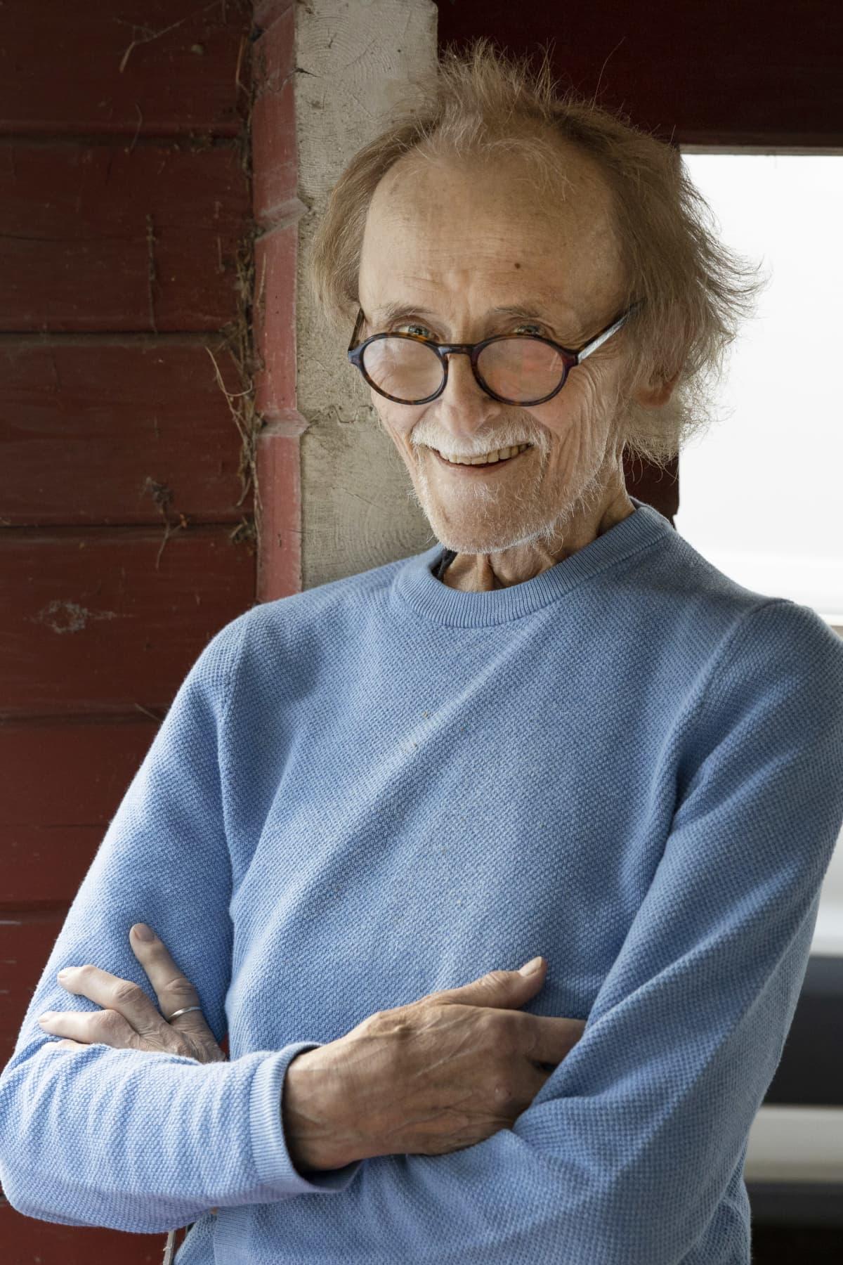 Seppo Kahilainen katsoo hymyillen kameraan silmälasiensa yli.