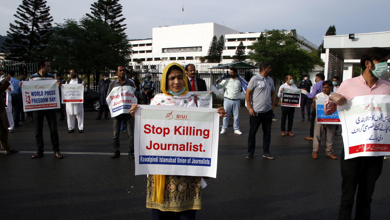Nainen pitelee kylttiä, jossa vaaditaan loppua toimittajien tappamiselle. Kuvassa myös muita mielenosoittajia.