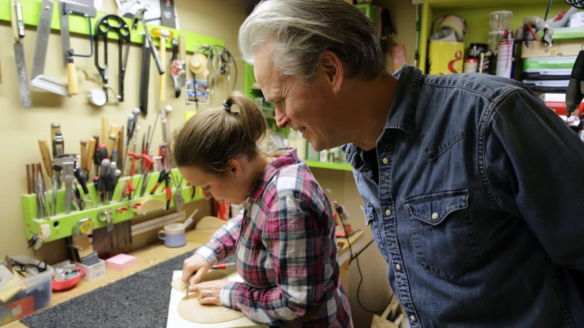 Mies katsoo, kun nainen rakentaa ukulelea