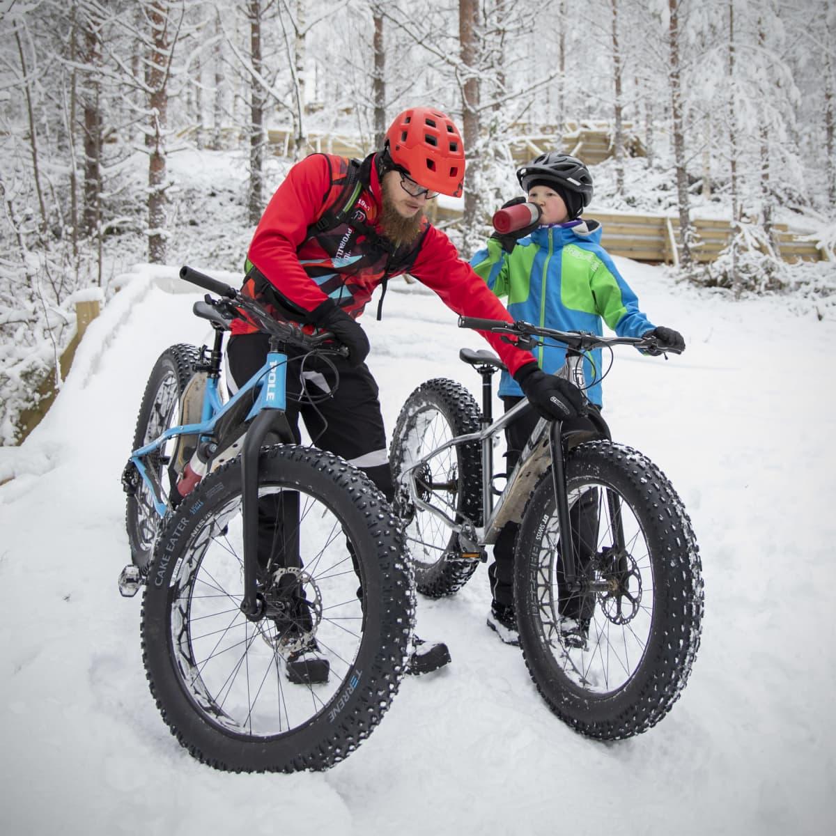 Sami ja Paavo Korhonen fatbike-pyöriensä äärellä lumisessa metsässä.