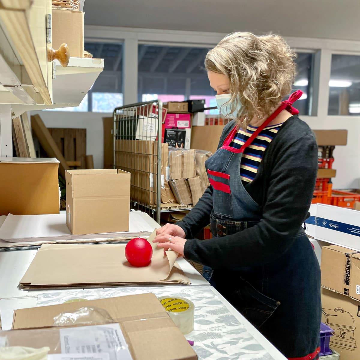 Riia Laitinen pakkaa Karoliina kynttilöitä verkkokaupan asiakkaille.