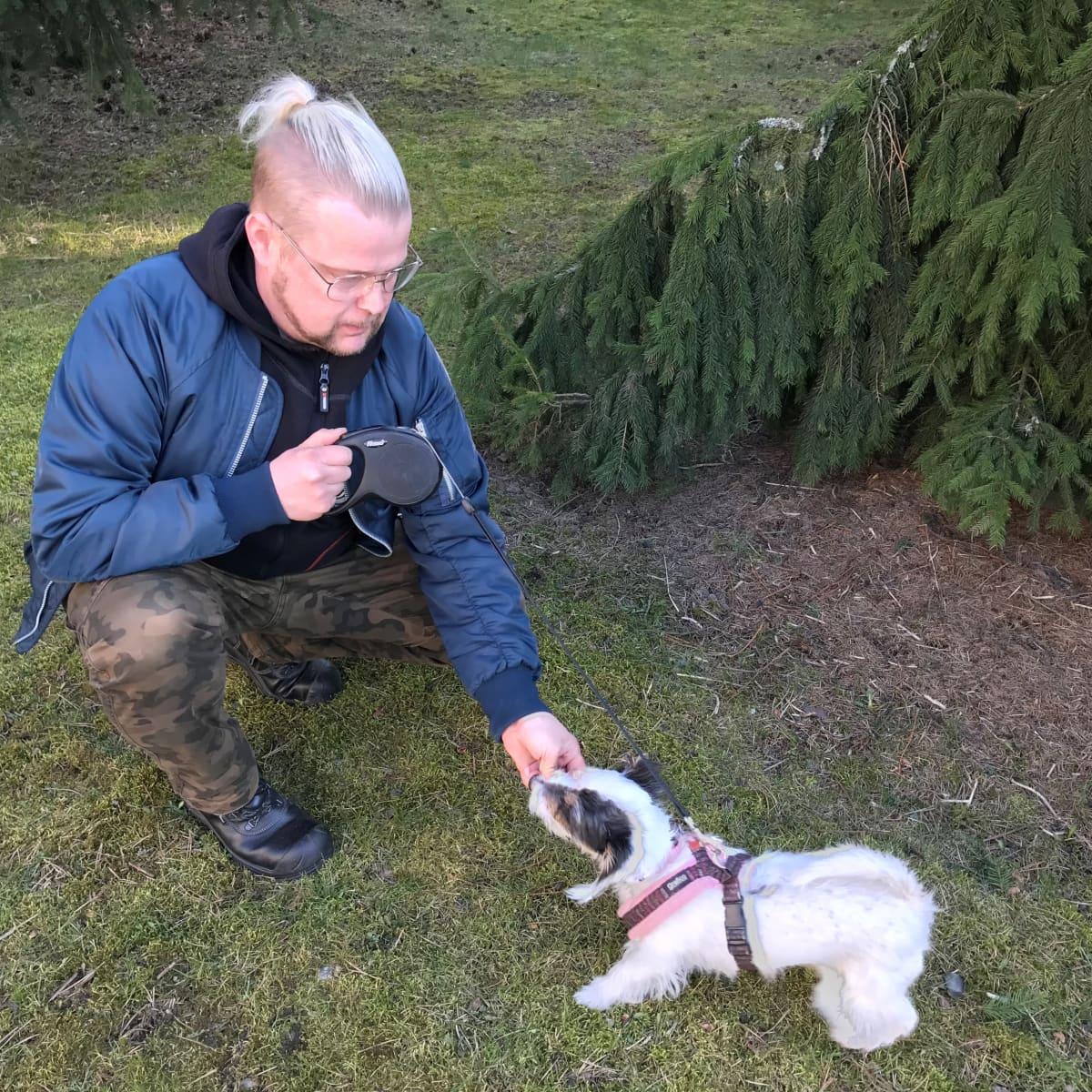 Mies leikkii ulkona koiran kanssa