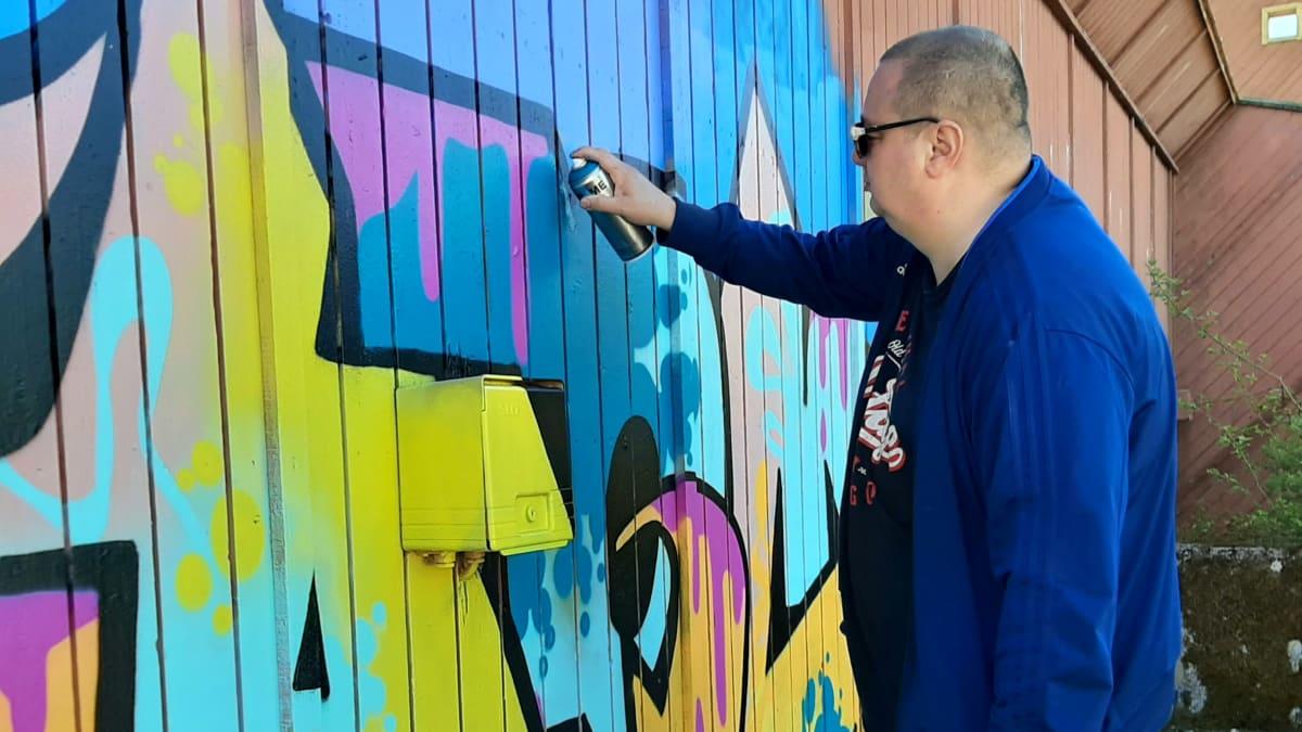 Jani Varismäki maalaa graffitia entisen Wasalandia-huvipuiston alueella Vaasassa.