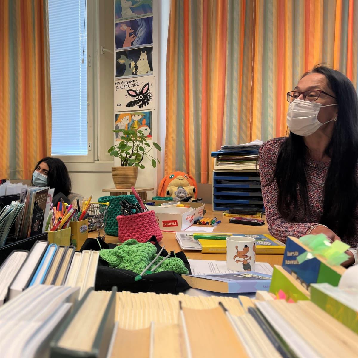 Naisopettaja opettajanpöydän takana