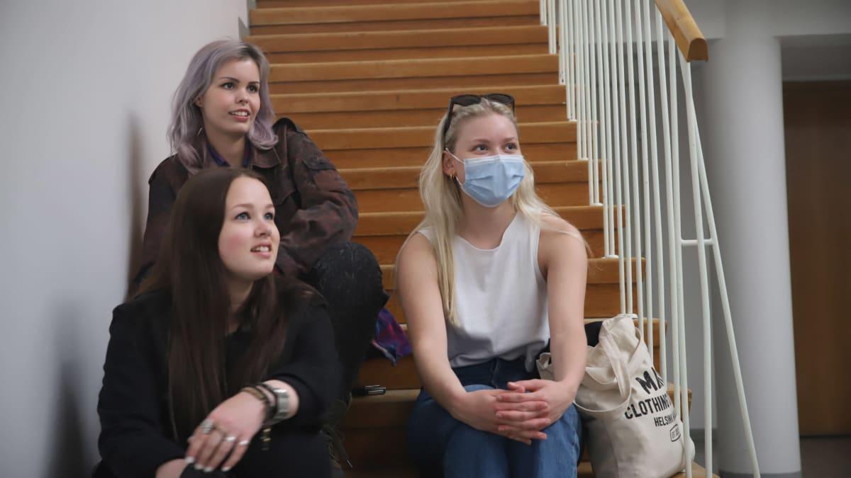 Näyttelijät Olympiada Hartikainen (ylh.), Veera Pyykkö (alh. vas) ja Elli Arstila istuvat portailla Lovi-sarjan kuvaustauolla.