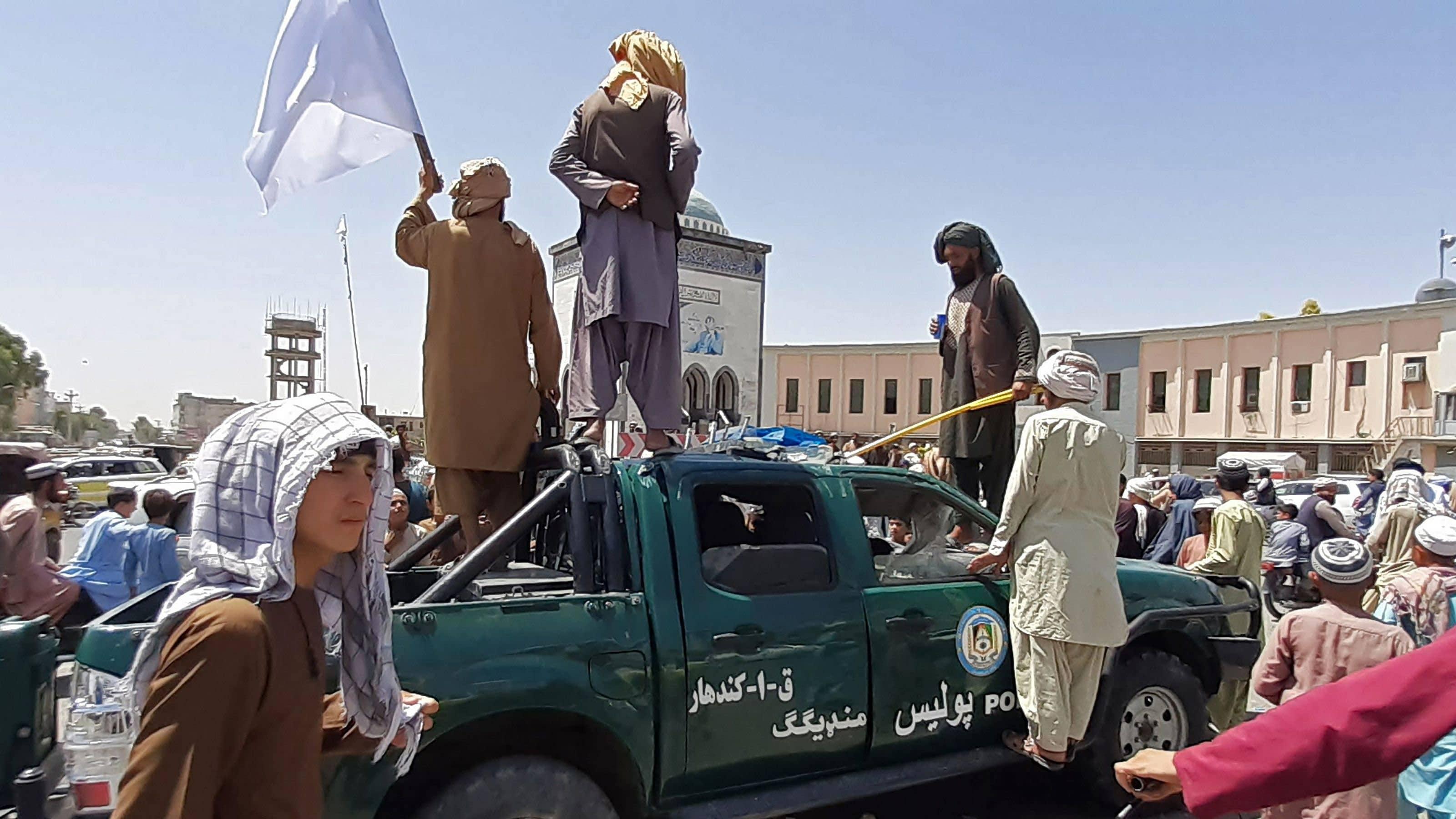 Taliban-taistelijat seisovat vaurioituneen poliisiauton päällä.