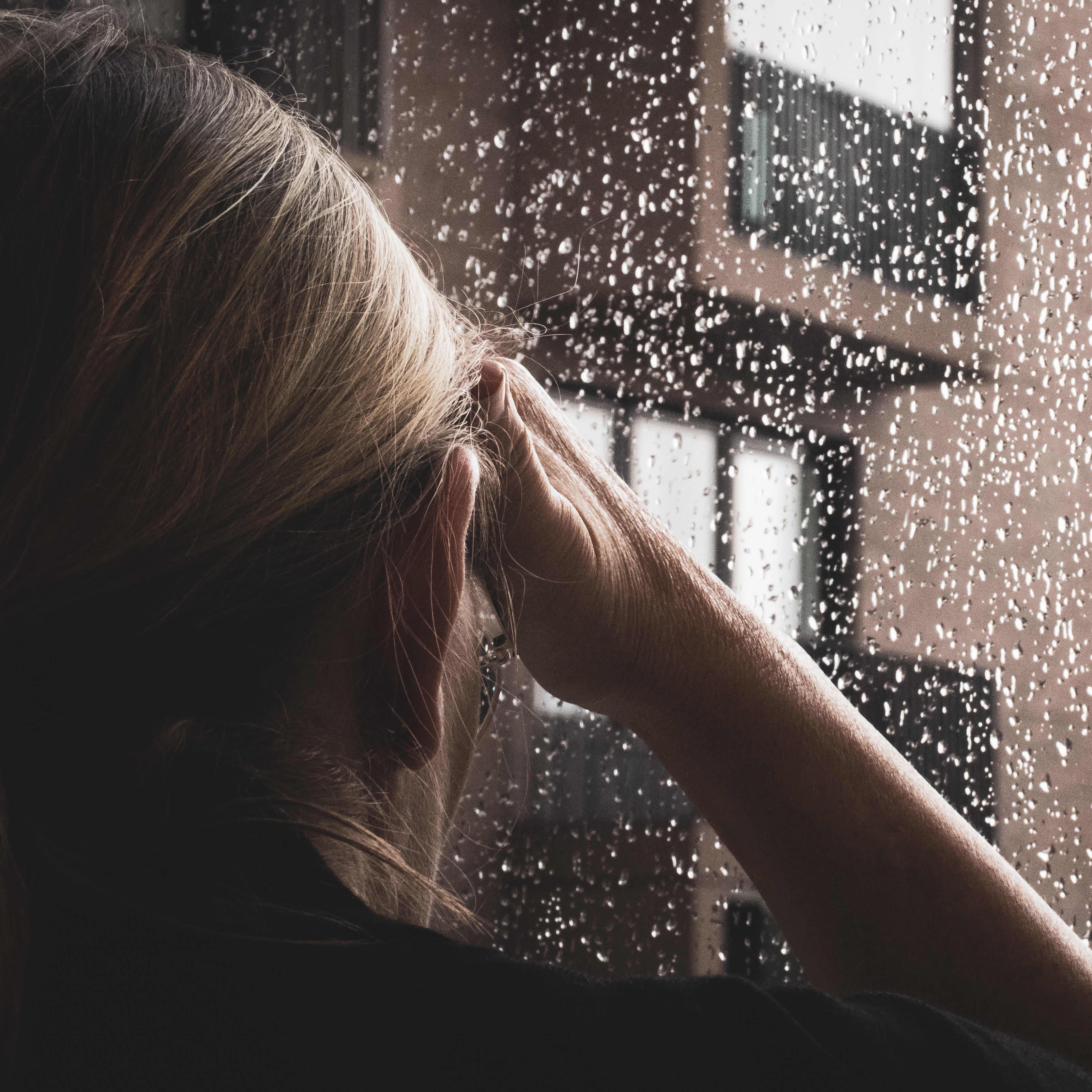 Nainen katselee sateisesta ikkunasta ulos.