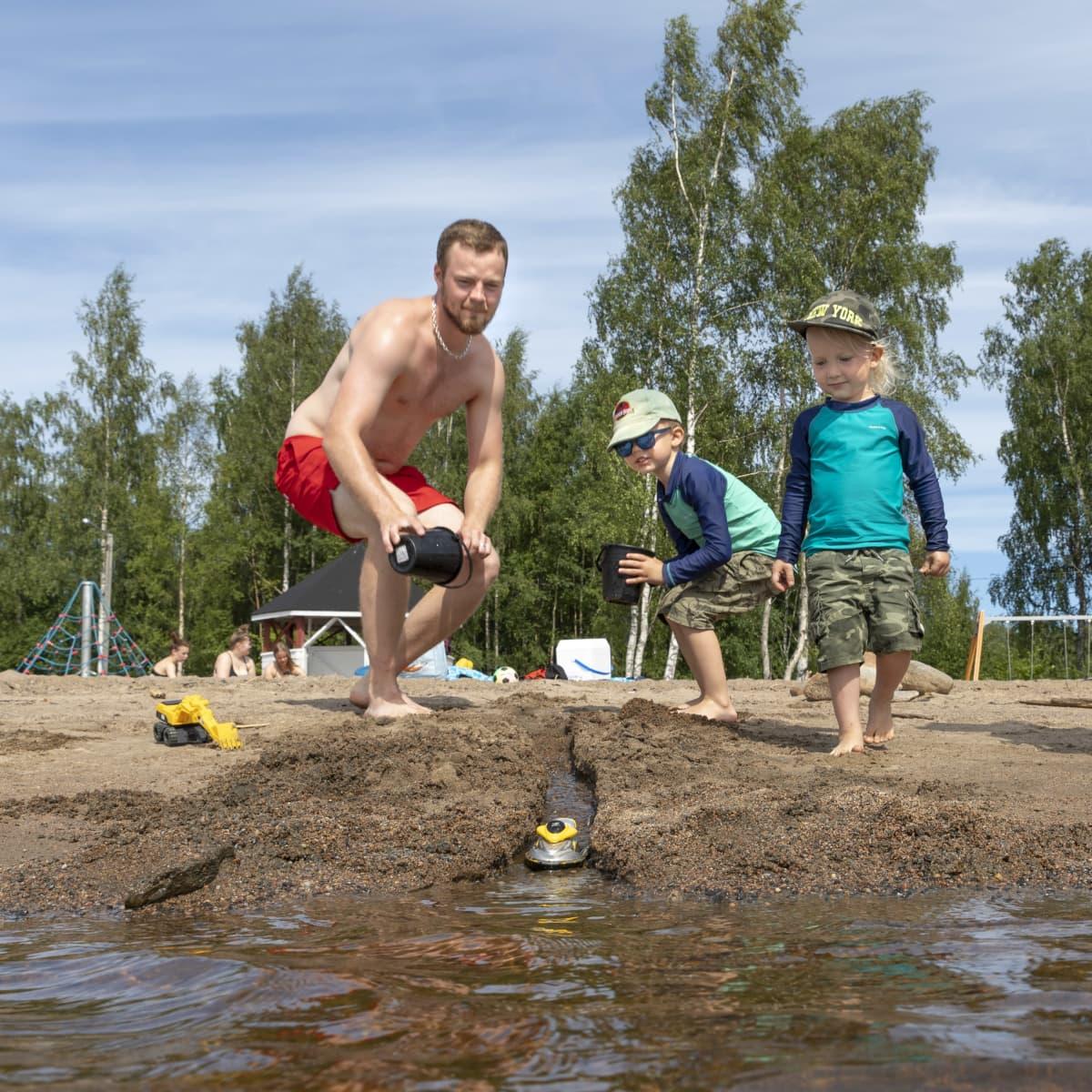 Isä ja pojat leikkivät vedellä Kemin Mansikkanokan uimarannalla.