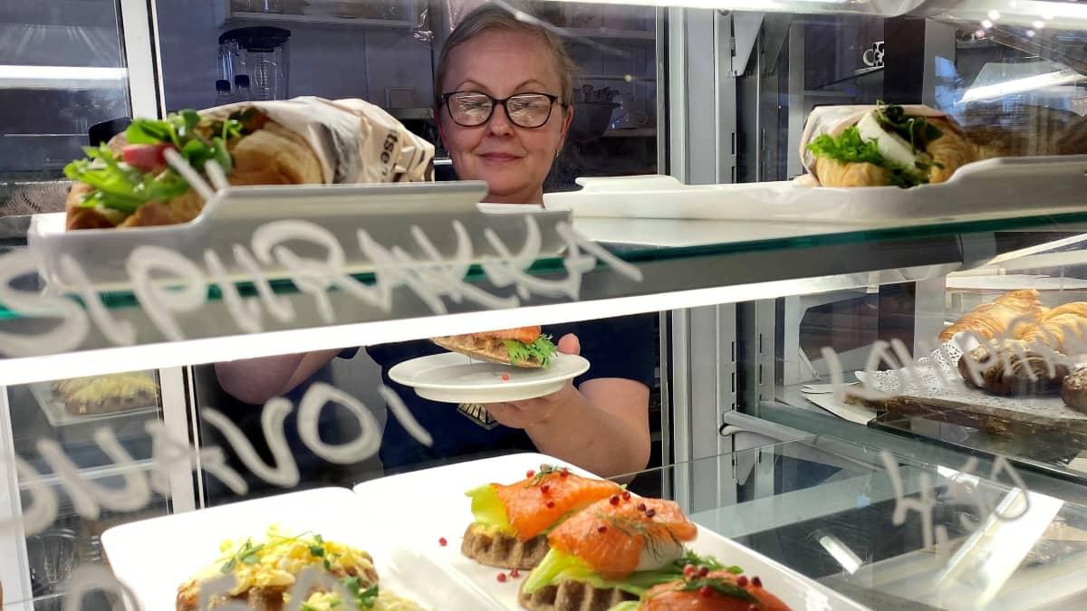 Kahvila Asemapäällikön pitäjä Soile Ylä-Jääski ottaa vitriinistä piirakkaa lautaselle. Etualalla lasin läpi näkyy piirakoita ja täytettyjä sämpylöitä.