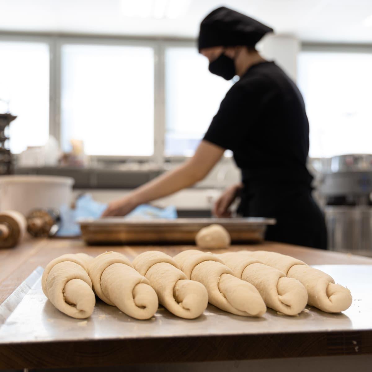 Leipomoalan opiskelija Saimaan ammattiopisto Sampon keittiössä tekemässä leivonnaisia. Etualla juustovoisarvia.