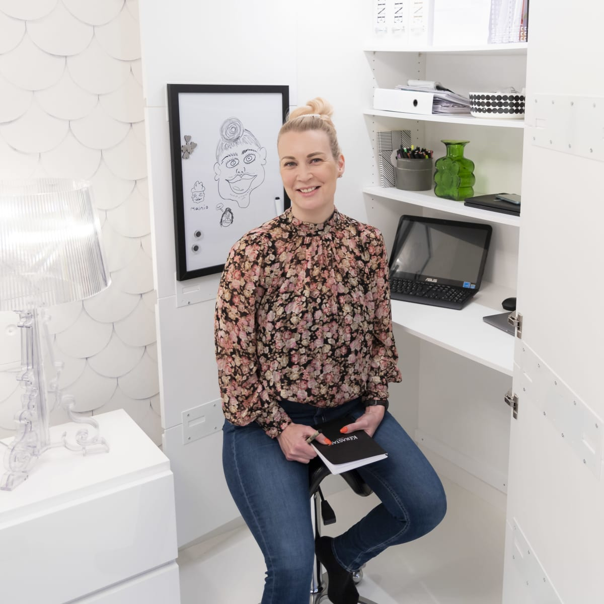 Marjo Ahola istuu etätyöpisteessään kotona. Hänellä on vihko ja työvälineitä käsissään. Työpöydällä on kannettava tietokone.