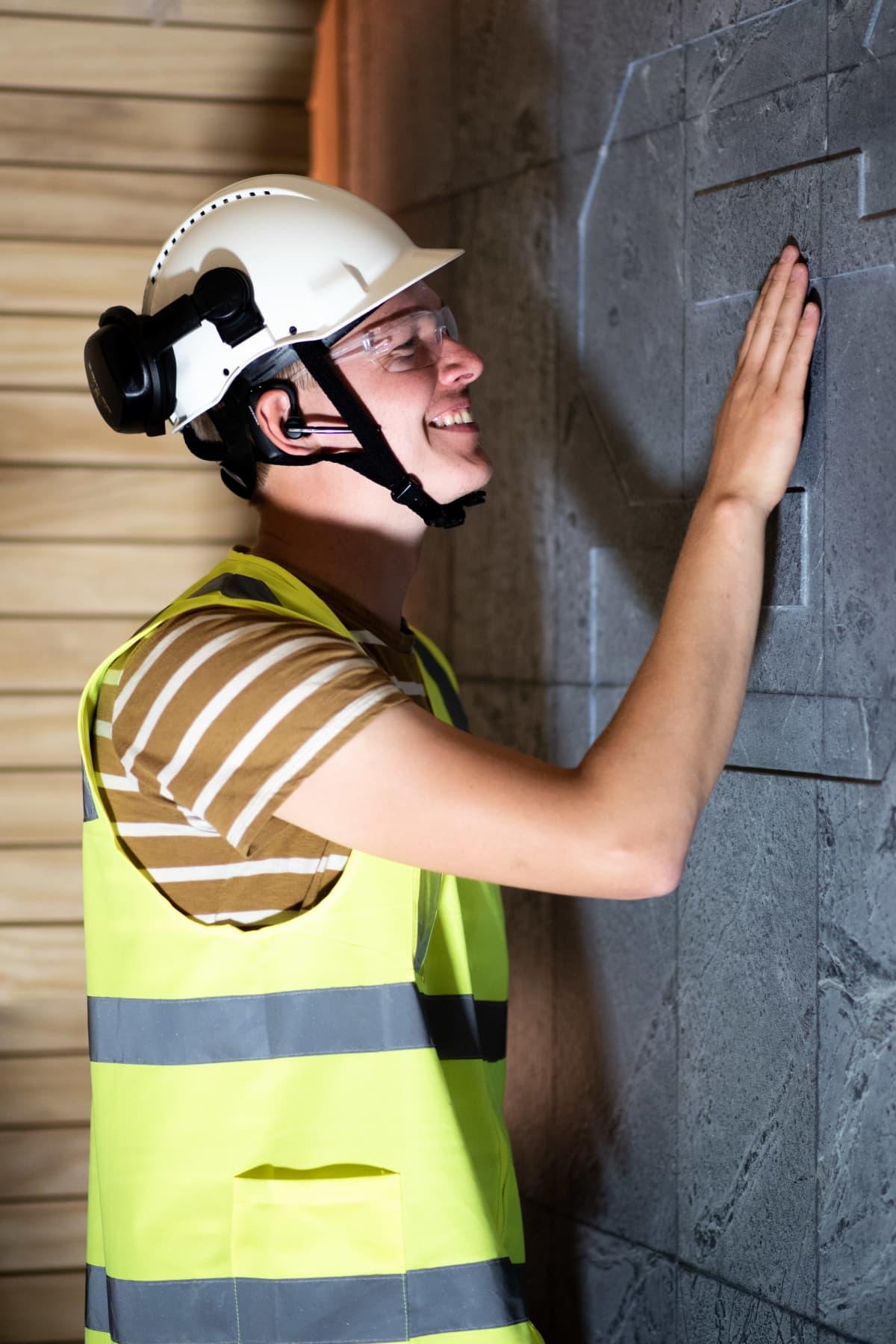 Miikka Kotilainen silittää Supercellin logoa saunan kiviseinässä.