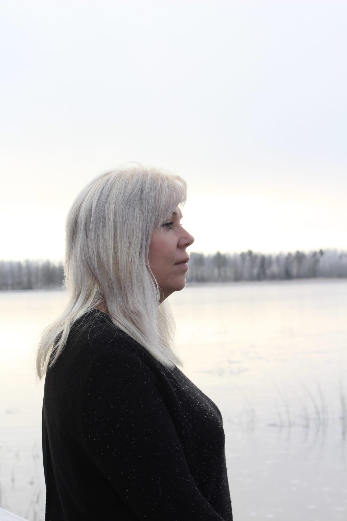 Natalia Alaspää katselee jäätyneelle Räyringinjärvelle.