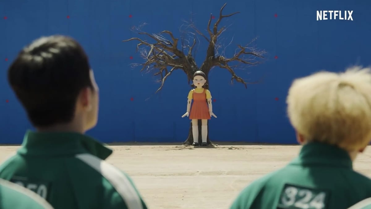 Nukkemainen tyttö puun alla, ihmiset tuijottavat.