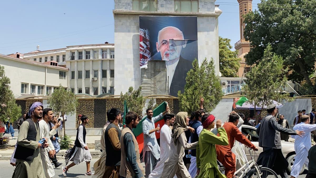 Afganistanilaiset juhlivat Afganistanin itsenäisyyspäivää Kabulissa, taustalla revitty juliste Afganistanin entisestä presidentistä.