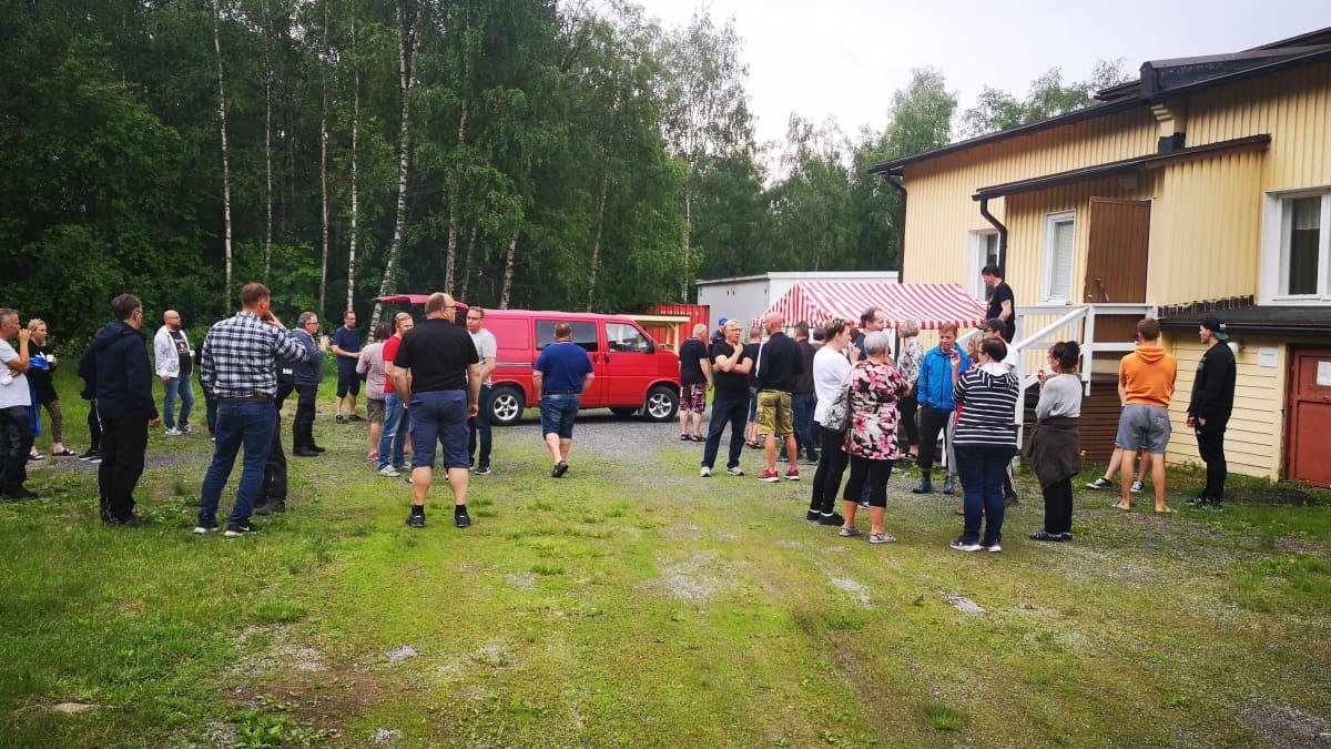 Veitsiluodon tehtaiden työntekijöitä seisomassa Rytikarin työväentalon edustalla ennen paperiliittolaisille tarkoitetun tilaisuuden alkua.