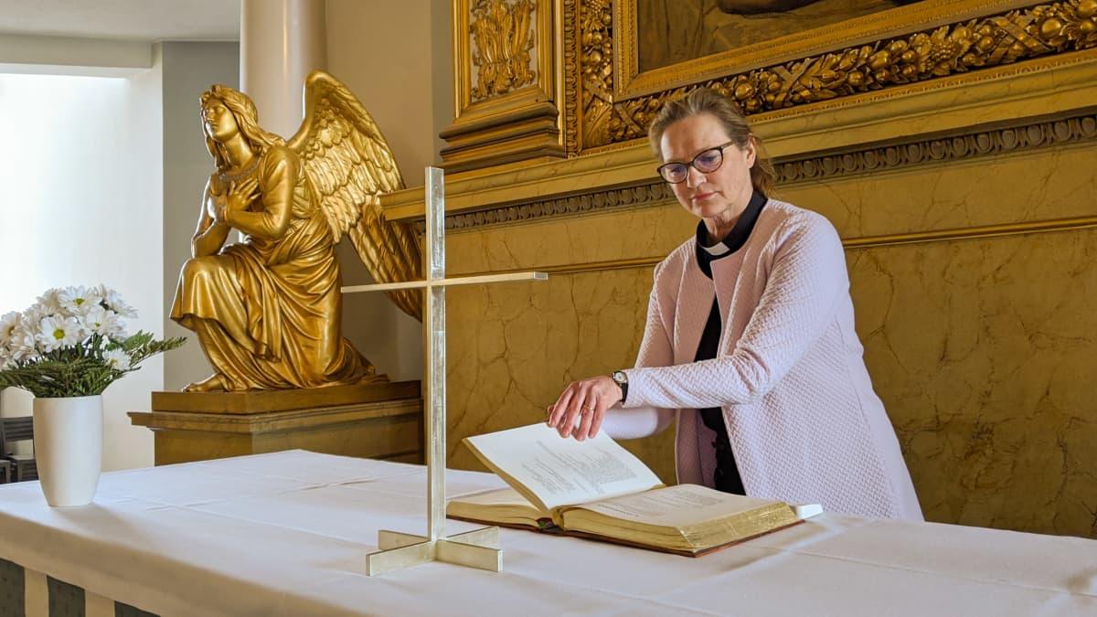 Maija Kuoppala, kappalainen, katselee raamattua Tuomiokirkon alttarilla.