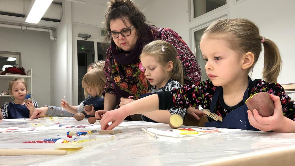 Kuvassa lapsi maalaa perunalla kangasta.
