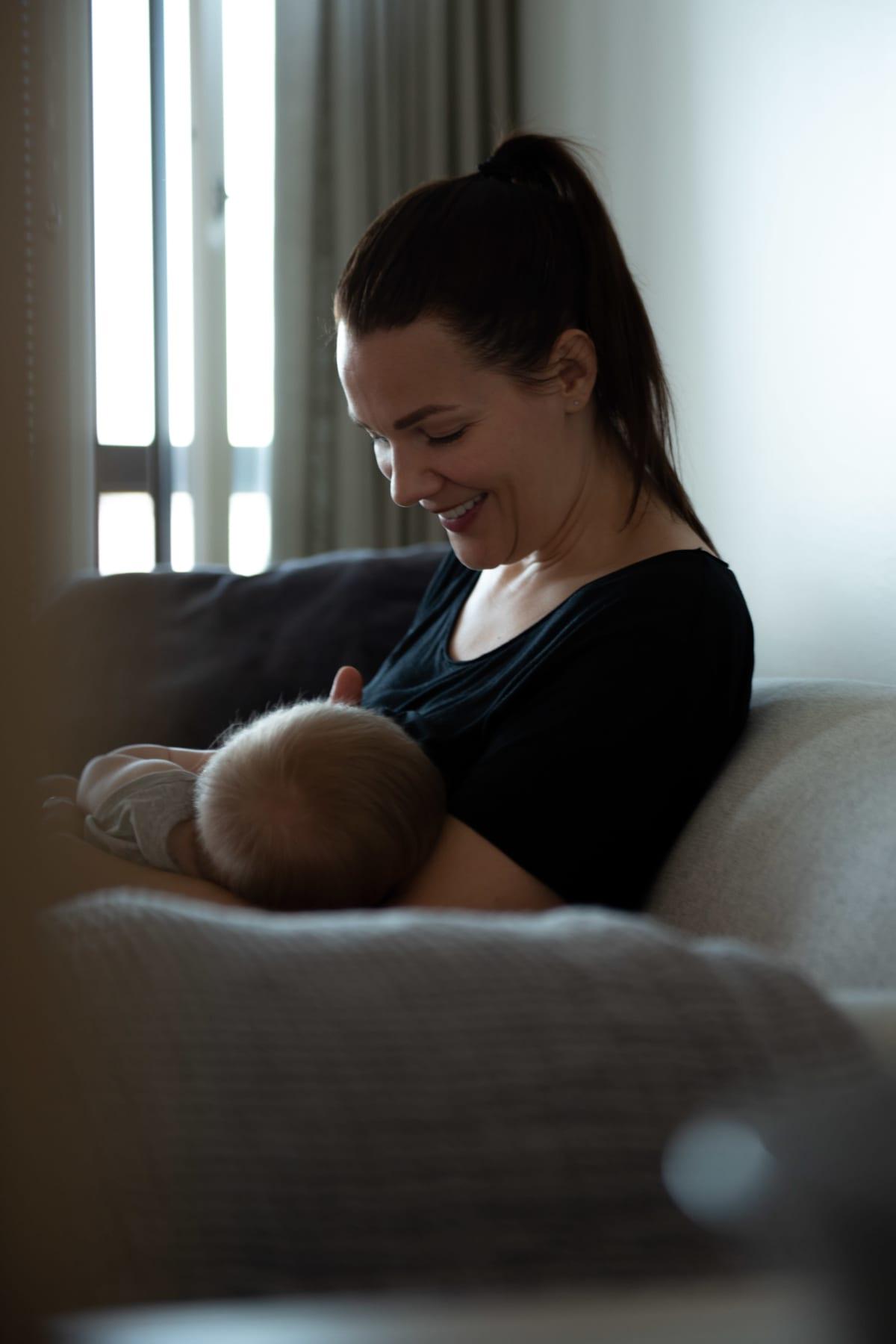 Outi Ellilä imettää lastaan sohvalla.