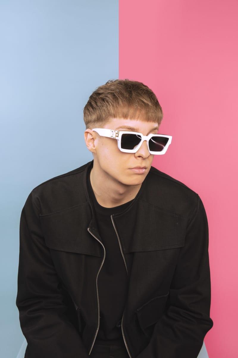 Artisti William aurinkolasit päässä turkoosilla ja pinkillä taustalla.