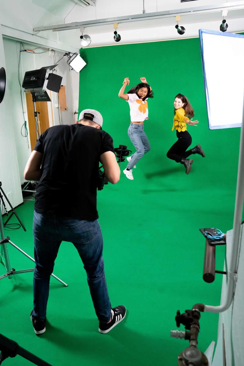 Kaksi naista hyppäämässä ilmaan kameran edessä studiossa.