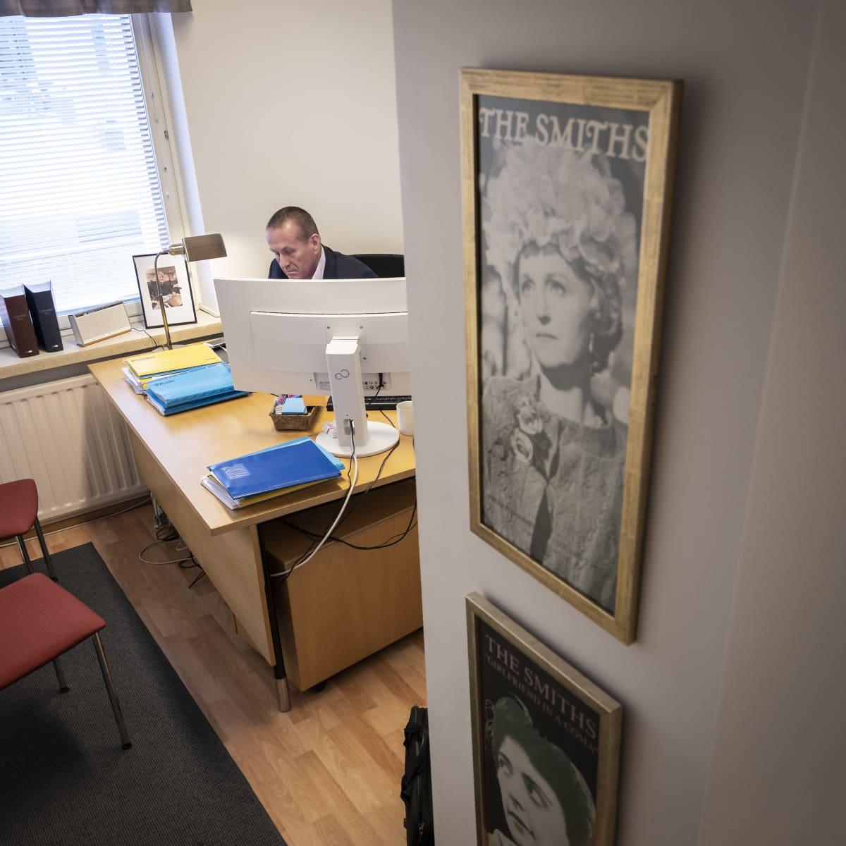 Mies istuu työhuoneessaan pöydän ääressä.