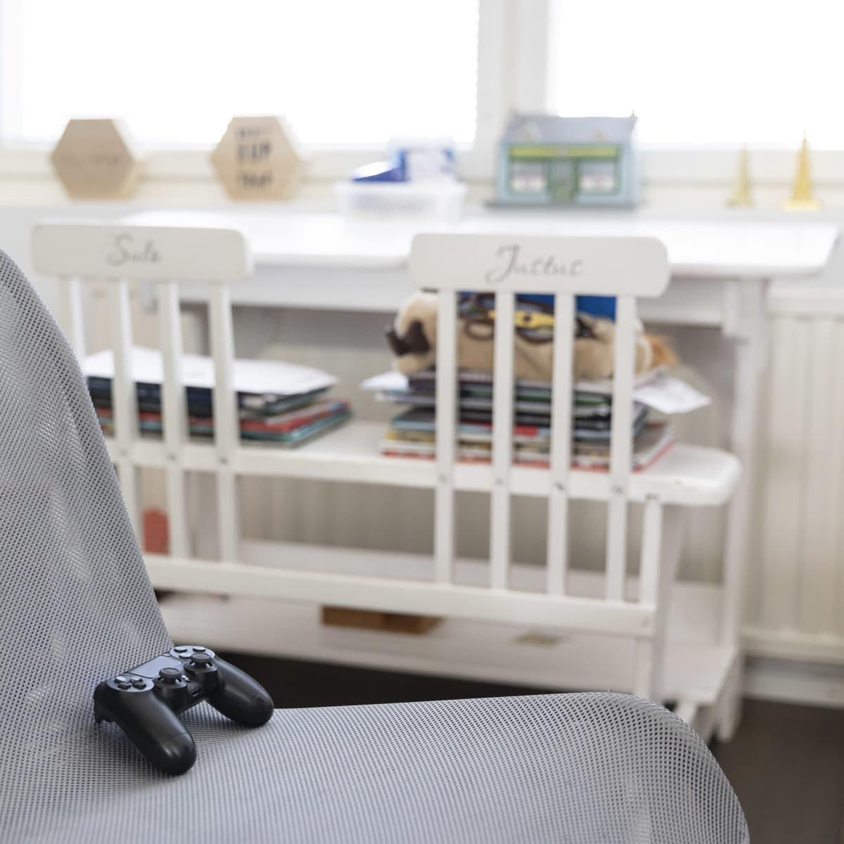 Playstation-ohjain tuolilla. Taustalla vanha pulpetti.