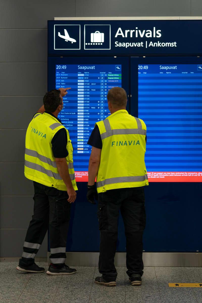Finavian työntekijöitä katsoo saapuvien lentojen aikataulua.