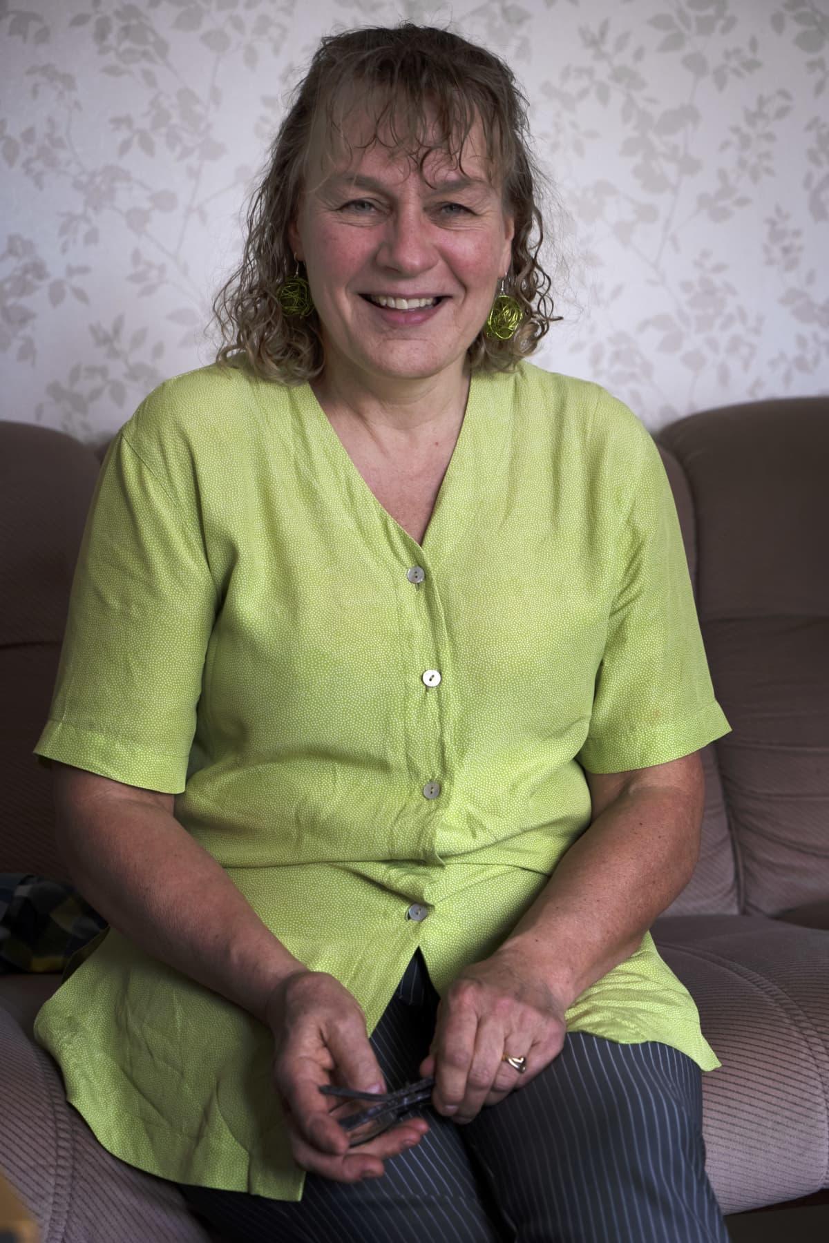 Brottaren Arvi Savolainens mamma Elina är iklädd en grön skjorta och sitter i en soffa. Hon skrattar.