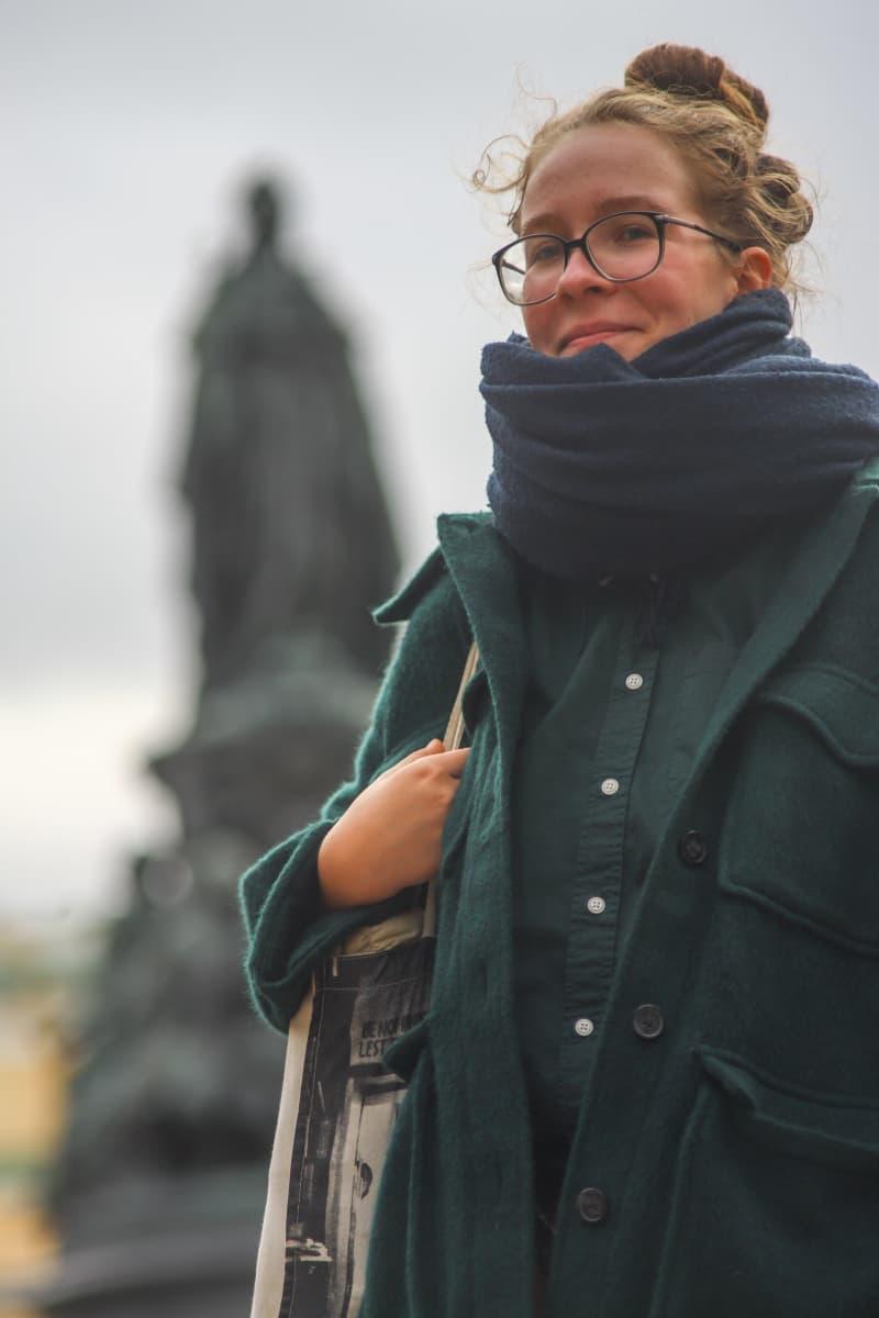 Tasja Kondratjeva katoo kameraan, taustalla Katariina Suuren patsas epätarkkana.
