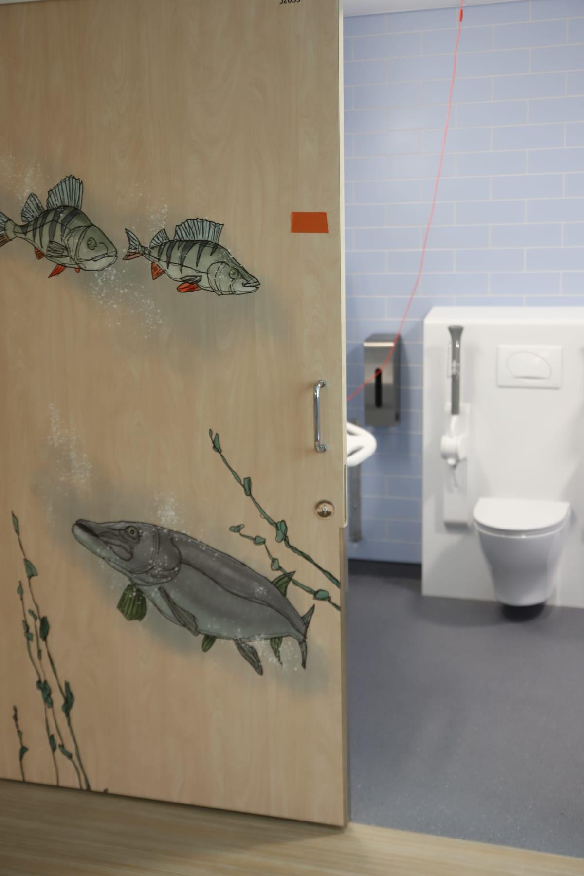WC-tilojen ovessa kalan kuvia